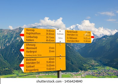 Yellow tourist sign on the top of Harder Kulm, Interlaken, Switzerland. The information sign specifies the directions and distances. Amazing summer Alpine landscape in background. Swiss Alps, tourism