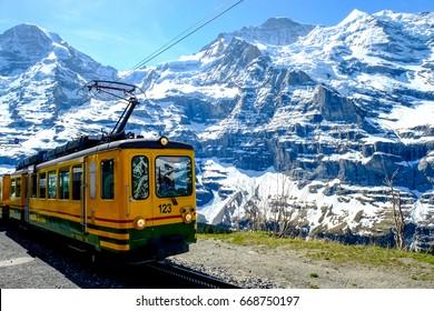 Yellow tourist train coming down from the Jungfraujoch with nice mountain view, Interlaken Switzerland