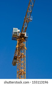 Yellow tower crane against the clear blue sky