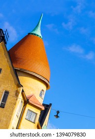 Yellow tower with red tile roof of the old 1800s building with tilted horizon