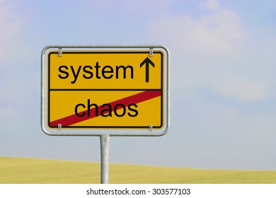 """Yellow town sign with text """"system chaos"""""""