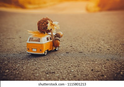 Yellow toy bus rides on asphalt road with acorn and autumn leaves. the concept of the autumn season.  Russia, Saransk, September 2017.