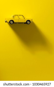 Yellow toy car on a yellow background with long and side shadow.