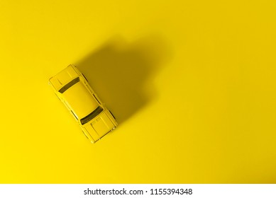 Yellow toy car top view on a yellow background with long and side shadow.