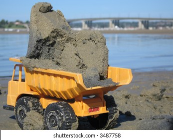 Yellow toy dump truck in the sand carrying a load with view of beach and bridge