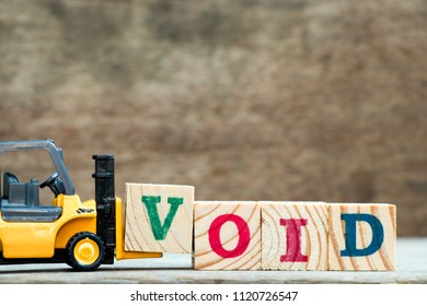 Yellow toy forklift hold letter block V to complete word void on wood background