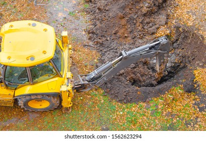 Yellow tractor excavator digs a pit with a bucket, accident. Breakthrough underground. Autumn winter top view