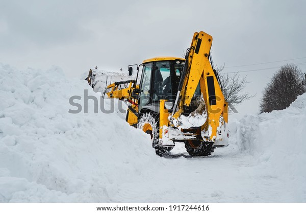 Yellow tractor excavator with a large bucket clears a snowy road from snow