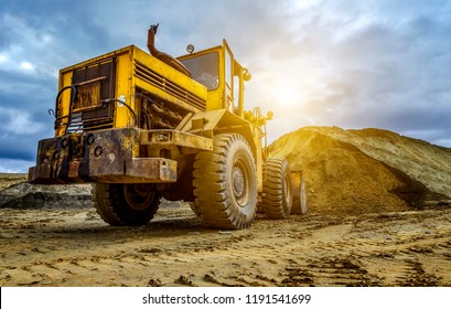Yellow tractor loader is picking up a bucket of earth, mechanical, ladle with earth and sun