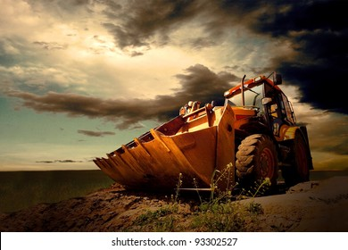 Yellow tractor on sky background