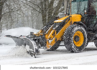 Yellow tractor with snowplow removing snow during heavy snowfall. Winter time street maintenance in hard weather conditions. Blizzard, traffic