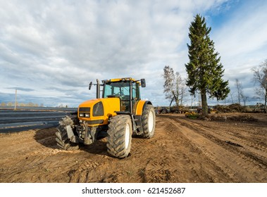 Yellow tractor stay at the field after works