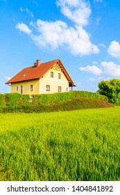 Yellow traditional house with red tile roof on green meadow in spring landscape of Burgerland in Strem village, Austria
