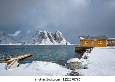 Yellow traditional rorbu house in Sakrisoy  fishing village in winter on Lofoten Islands, Norway