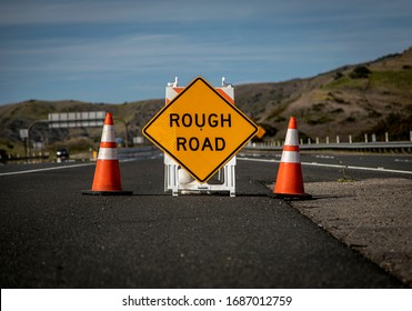 Yellow traffic control sign stating Rough Road on highway shot in late afternoon sun. A car is visible blurred driving past. Sign could be used as a metaphor for life or business or coronavirus