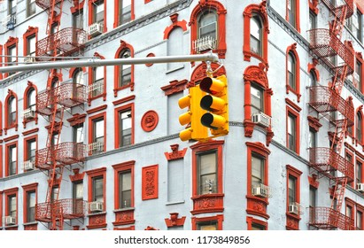 Yellow traffic light hanging on the pole with bacground of old colorful classic red and white building with ornaments, facade, balcony, architecture and windows in  Downtown, LowerManhattan