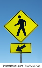 Yellow traffic pedestrian sign with man and directional arrow on a blue sky background