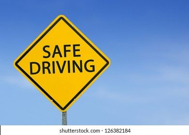 """Yellow traffic sign """"Safe driving"""" on the sky background"""