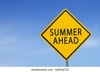 "Yellow traffic sign ""SUMMER AHEAD"" on the sky background"
