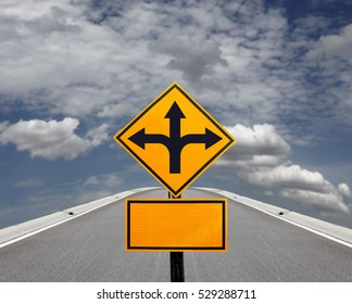 A yellow traffic signpost with imprint of a three way arrow symbol and a blank board against a highway vanishing into a blue cloudy sky for the concept: Making Choices.