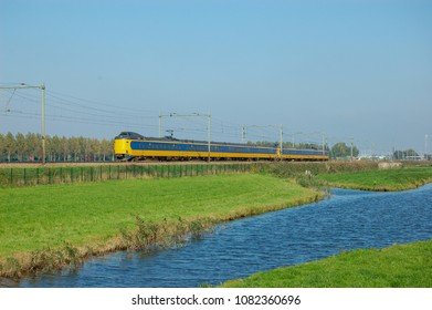 Yellow train driving through meadow. In the foreground a ditch. The Netherlands.