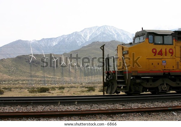 yellow train engine and cars heading into the moutains