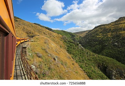 Yellow train entering a tunnel - Taieri River Gorge, New Zealand