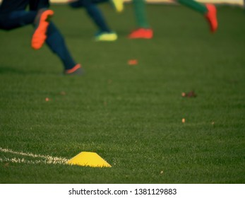 Yellow training cone. Soccer training equipment on green grass field