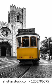 Yellow tram against the Lisbon Cathedral in Alfama district of Lisbon, Portugal. Black and white photo with coloured tram