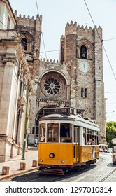 Yellow tram in front of church in Lisbon city, Portugal
