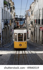 Yellow tram in Lisbon, Portugal, driving in a very steep street, one of the main tourist attractions