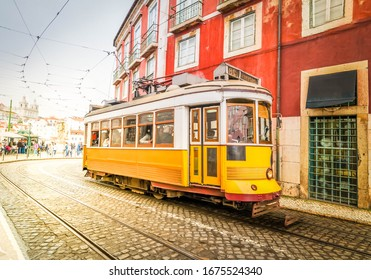 yellow tram on narrow street of Alfama district, Lisbon, Portugal, toned