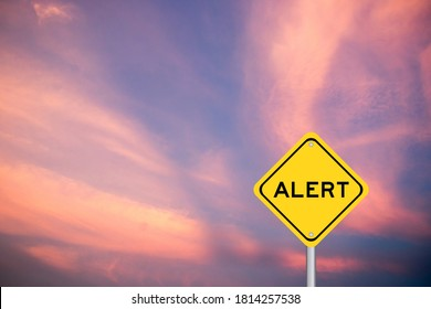 Yellow transportation sign with word alert on violet sky background