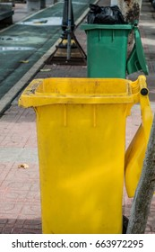 Yellow trash and green bin in the back.