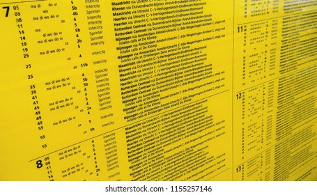 Yellow travel information board with all departing trains from Amsterdam Central Station in the Netherlands. (time table)