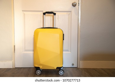 Yellow travel suitcase in the bedroom on the door background - relaxing time, holidays, weekend and traveling concept.