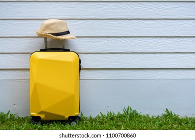 Yellow travel suitcase with hat on the wooden background - relaxing time, holidays, weekend and traveling concept.