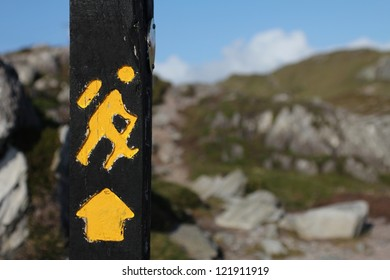Yellow trekking sign on a wooden pole