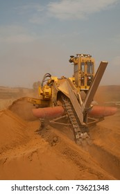 Yellow trencher digging a deep pipeline trench on construction site
