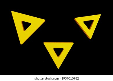 Yellow triangle shaped wooden blocks with black background
