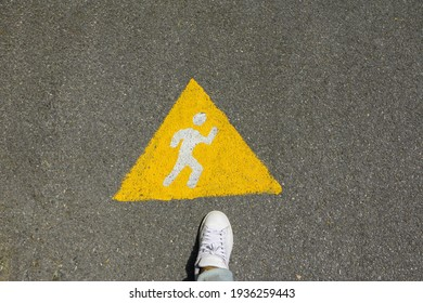 Yellow triangle symbol with color white of running people on asphalt road way with right foot wear white shoes