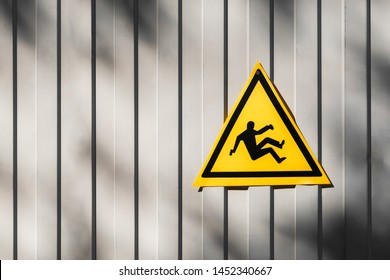 Yellow triangular road sign warning for risk of falling hanging on the gray fence. triangular traffic sign warning for danger of falling or steep grade. Yellow falling man -Warning hazard sign