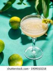 gelber tropischer Cocktail auf Laub-Hintergrund, Schatten von der Sonne. grüner Hintergrund
