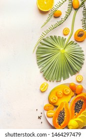 Yellow tropical fruits plate on white table with tropical leaves. Food background. Healthy eating. Sommer fruits food. Halved papaya. Top view. Copy space