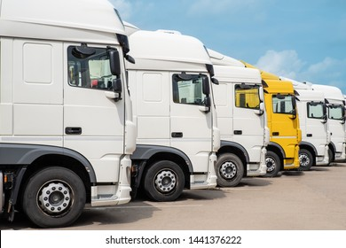 Yellow truck among white trucks lined up side view
