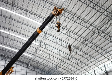 Yellow truck crane boom with hooks in the warehouse.  Indoor lighting. The background is the new roof of warehouse.