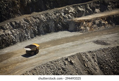 Yellow truck drives along a dirt road in an open cast mine in New South Wales, Australia. Barrick Cowal Gold Mine.