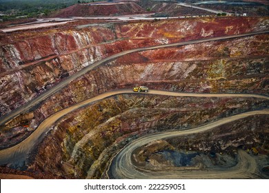 Yellow truck drives along a winding path inside an open cast mine in New South Wales, Australia.