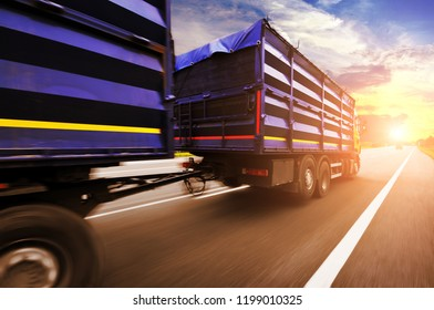 Yellow truck in motion with a blue container driving on the countryside road against night sky with sunset