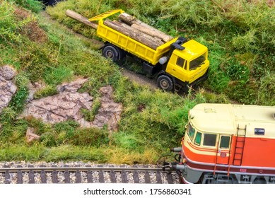 Yellow truck on model train railroad layout in H0 scale with wood near locomotive